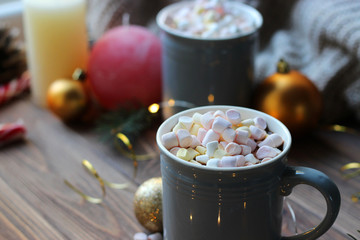 Hot cocoa, christmas accessories and garland on a wooden table. Warming drinks