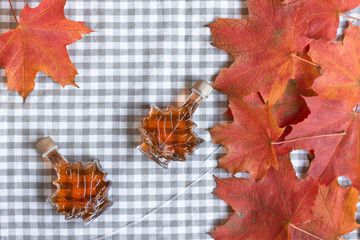 Maple syrup in a bottle in a shape of maple leaf. Red maple leaf background.