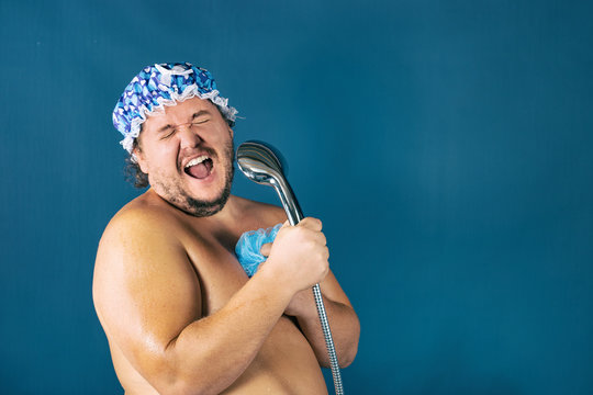 Funny fat man in blue cap sing in the shower