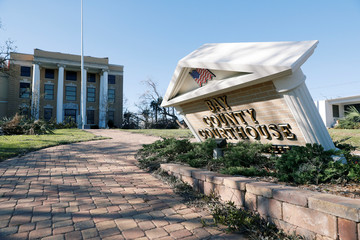 A sign stands askew in the aftermath of Hurricane Michael at the Bay County Courthouse in Panama City
