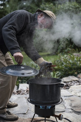A man cooking lobsters outside in a lobster steamer