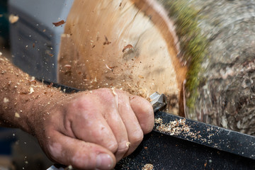 wood sawdust shavings squirting while creating timber bowl on turnery