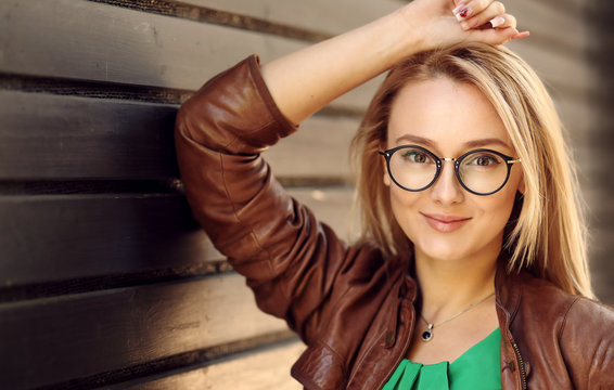 Smiling Attractive Blonde Girl With Natural Face Makeup Wearing Stylish Fashion Optical Eye Glasses. Minimalist urban clothing style, mockup for Optical Eye Glasses