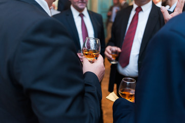 Businessmen drink cognac and whiskey