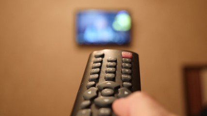 Smart tv and hand pressing remote control. hand pressing buttons on the remote for the TV.