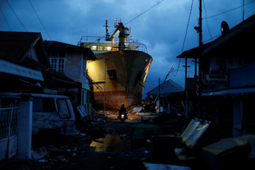 A motorcycle drives in front of a stranded ship in the port hit by tsunami on the coastline in Palu