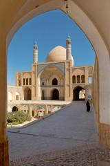 Muslim woman walking in Iran at Kashan Mosque