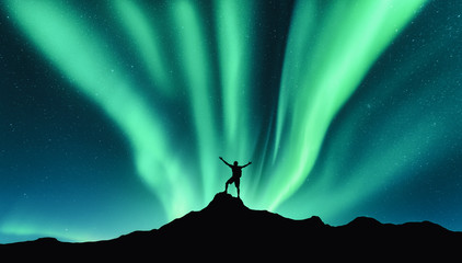 Zelfklevend Fotobehang Groen blauw Northern lights and silhouette of standing man with raised up arms on the mountain in Norway. Aurora borealis and happy man. Sky with stars and green polar lights. Night landscape with aurora. Concept