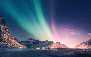 Tuinposter Noorderlicht Green and purple aurora borealis over snowy mountains. Northern lights in Lofoten islands, Norway. Starry sky with polar lights. Night winter landscape with aurora, high rocks, beach. Travel. Scenery