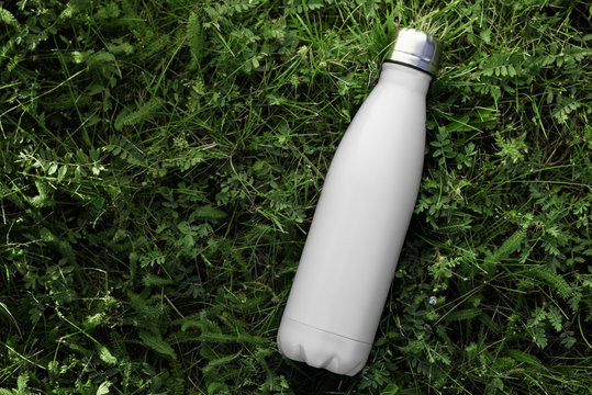 Stainless thermos water bottle isolated on green grass outdoor. White matte color. Horizontal photo without effects.