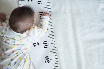 Baby Body and measuring tape: concept of baby growth, height, development.