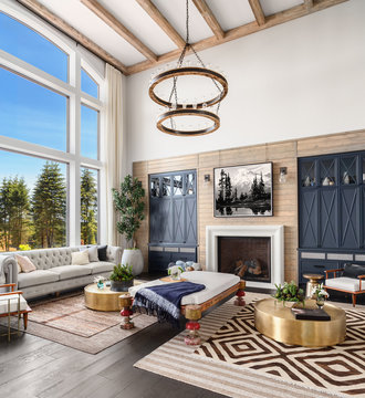 Beautiful Living Room in Luxury Home with Elegant Chandelier, Fireplace, Hardwood Floors, and Tall Ceiling. Has Large Bank of Windows with Exterior View of Blue Sky and Trees.