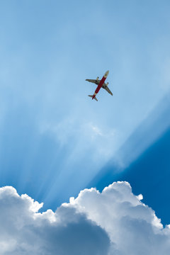 A worm's-eye view of an airplane on sky with sunlight
