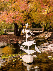 A group of origami cranes displays on a pond