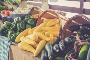 Fresh harvest vegetables and fruit attractively displayed in baskets at farmers market in vintage setting