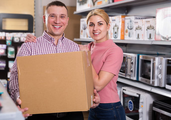 Couple  holding  packed purchases in store of household appliances