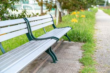 遊歩道のベンチと道に咲く彼岸花