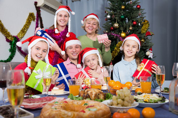 Happy family with kids posing with gifts at Christmas