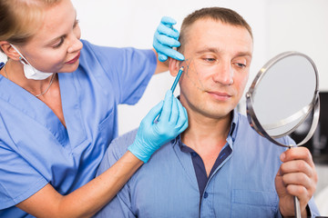Female specialist is marking zone on face of client