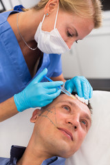 Female doctor is doing injection to patient in skin of face