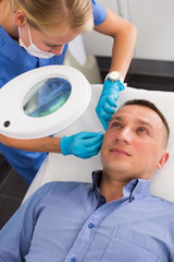 Female doctor is doing cleaning skin procedure to client