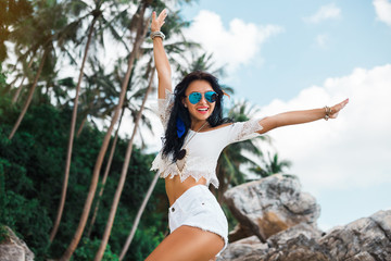 beautiful girl in a Boho style dressed shirts shorts light cape bracelets necklaces, in hair decorative feathers colored, spread her hands in the sides against the sea and rocks, a sense of freedom