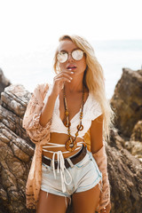 beautiful girl in a Boho style dressed shirts shorts light cape bracelets necklaces, in hair decorative feathers colored, standing sensual pose against the background of sea cliffs, sense of freedom