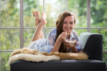 Healthy young woman lying on a couch holding a bowl of yogurt looking relaxed and comfortable