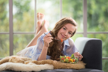 Healthy young woman lying on a couch holding a salad bowl looking relaxed and comfortable