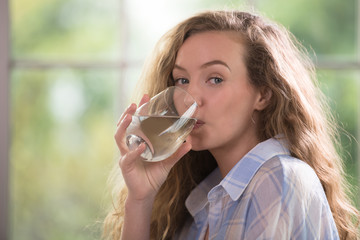Healthy young woman drinking water at home