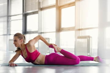 Beautiful young woman doing fitness exercises on mat