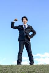青空をバックにガッツポーズをするスーツ姿の若いビジネスマン1人。元気、成功、ヤル気、挑戦イメージ