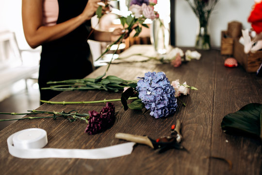 There are hydrangea, carnation and other flowers, scissors and  ribbon on the table in flower shop