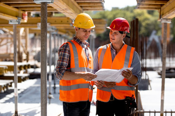 Two civil engineers dressed in orange work vests and helmets explore construction documentation on the building site near the wooden building constructions