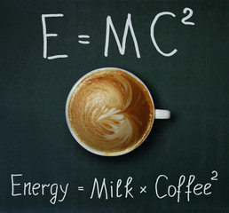 The cup of coffee with milk and two formulas. E = mc2. Black background.