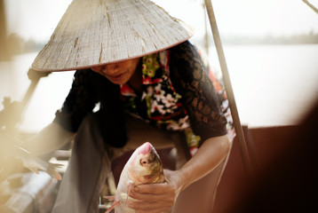 Vietnamese fisherwoman in conical hat (non la) holding fish and stepping out of boat somewhere on the Red River delta