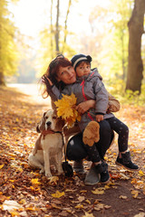 Mid age  woman with little girl and beagle walking  in the autumn park.