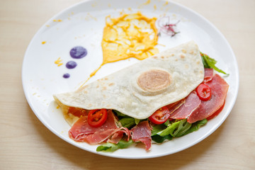 Delicious tortilla with jamon ham meat and fresh vegetables