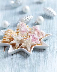 Christmas butter cookies with icing and sugar pearls. Bright wooden background. Close up.