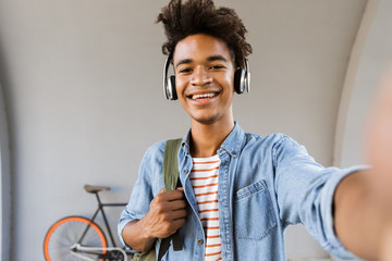 Smiling young african man with backpack outdoors