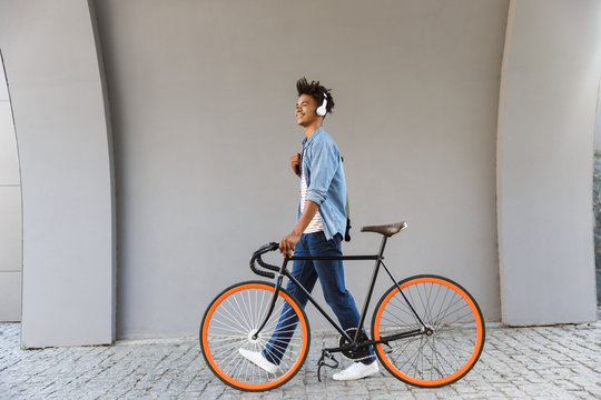 Smiling young african man outdoors, walking with bicycle