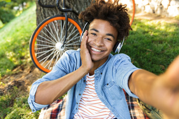Happy young african teenager with bicycle outdoors