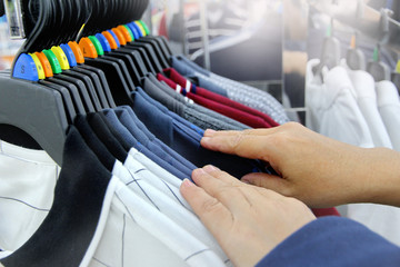 Using hand to choose a set of clothes wear by colour and size .