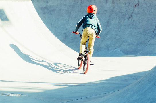 boy pedaling his bicycle in a bmx park