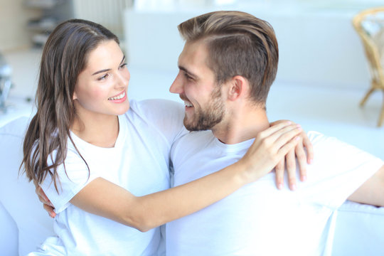 Happy young couple hugging and looking at each other at home interior.
