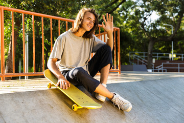 Photo of teen guy 16-18 in casual wear sitting on ramp with skateboard in skate park, during sunny summer day