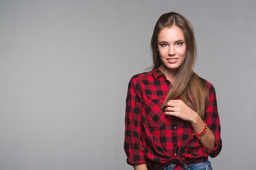 Young beautiful woman teenager in a red checked shirt and torn denim shorts