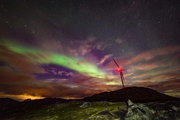 Aurora borealis being a wind turbine generator on top of a hill
