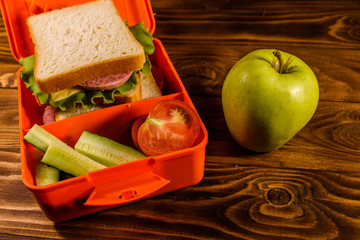 Lunch box with sandwich, cucumbers, green apple and tomatoes on wooden table
