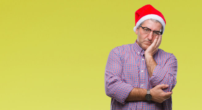 Handsome senior man wearing christmas hat over isolated background thinking looking tired and bored with depression problems with crossed arms.